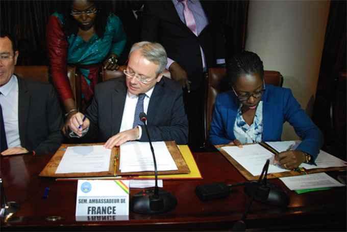 Joël Meyer, ambassadeur de la France et la ministre Kamissa Camara apposant leurs signatures